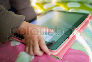 Hand of Asian boy playing Tablet fun