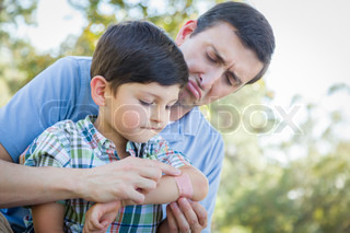 Loving Father Puts Bandage on Elbow of Young Son