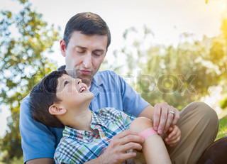 Loving Father Puts Bandage on Knee of Young Son