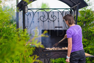 Young man fries steaks on the grill outdoor in his yard