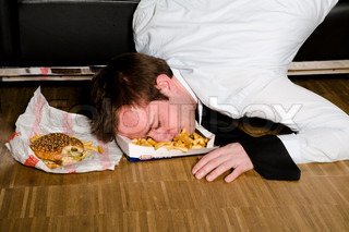 A tired office employee fell asleep while eating junkfood