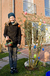 A caucasian girl decorating a tree with Easter eggs